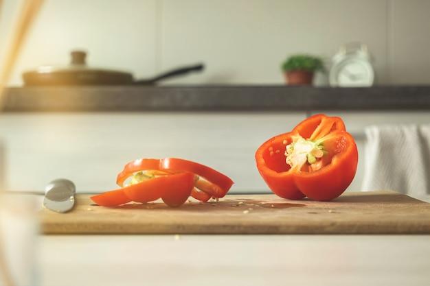 Tagliere con pepe rosso su uno sfondo di cucina moderna. peperone dolce affettato sul bordo di legno. ingrediente vegetale, cucinare cibo sano concetto foto