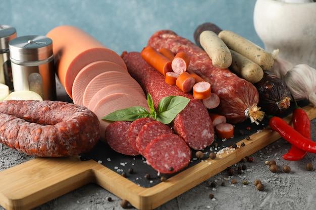 Tagliere con la salsiccia e le spezie sulla tavola grigia, fine su