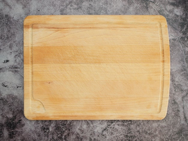 Tagliere in legno sul tavolo in marmo grigio.