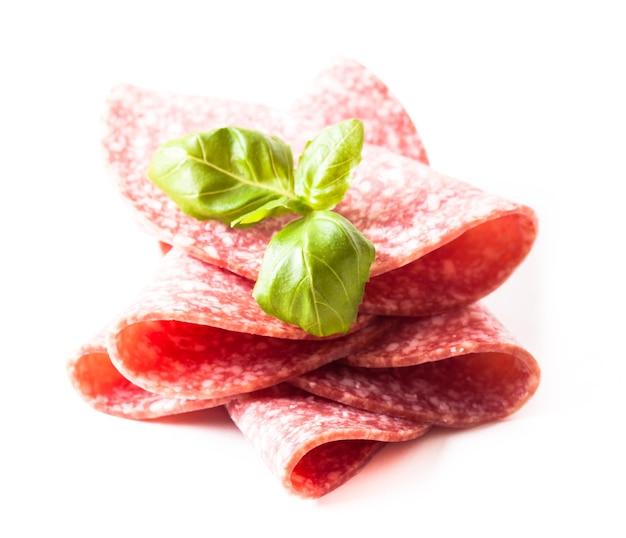 Tagliare le fette di salame freddo da vicino isolato su bianco