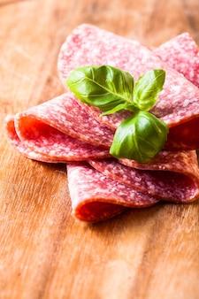 Taglio di fette di salame freddo da vicino su tavola di legno
