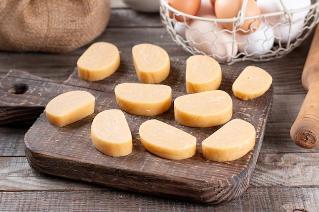 Tagliare la pasta con un coltello sul tavolo della cucina. concetto di cottura della pasta, biscotti, pizza,