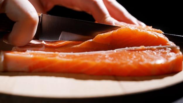 Tagliare il pesce a fette per cucinare il sushi