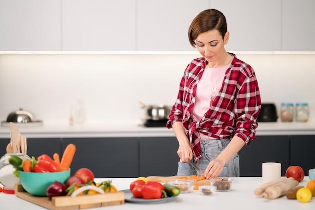 Tagliare la casalinga della carota fresca che cucina lo stufato di carne o il ragù che indossa una camicia a quadri