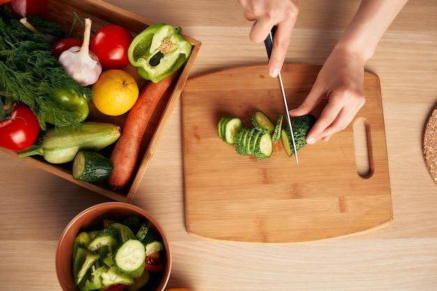 Tagliare le verdure fresche su un tagliere da cucina mangiare sano a casa