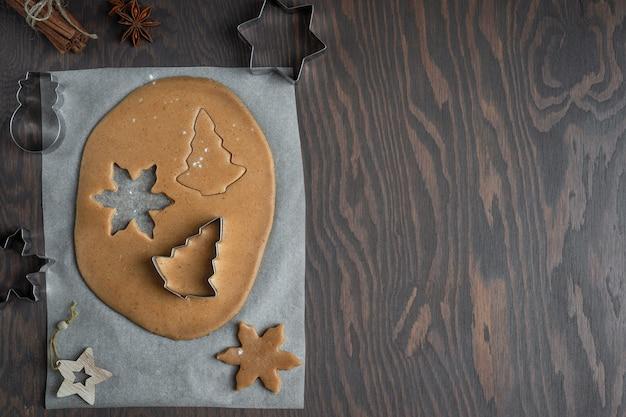 Taglio di biscotti di panpepato fatti in casa dalla pasta di pasticceria salata sulla tavola di legno con le frese