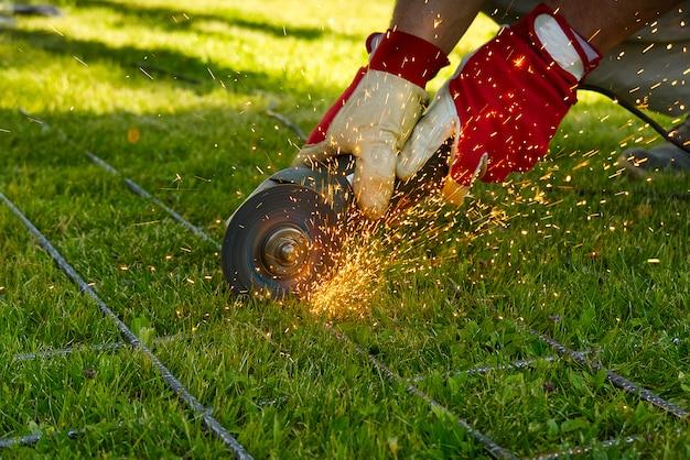 Rete metallica di taglio con smerigliatrice su erba verde. scintille da materiali di contatto. lavoratore esterno, tagliare la rete d'acciaio. processo con smerigliatrice angolare.