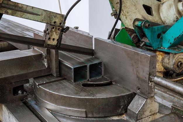 Taglio di profili e tubi in acciaio su una sega a nastro in produzione.