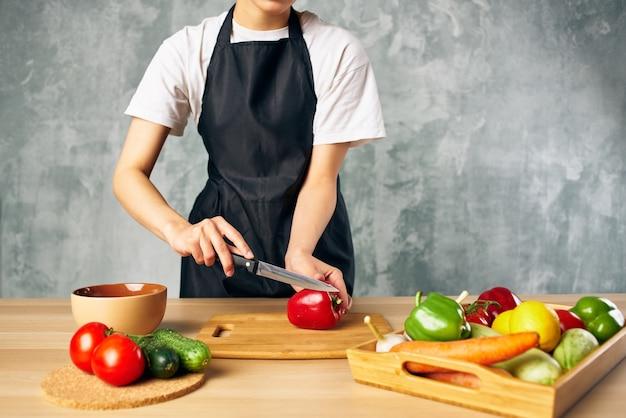 Tagliare le verdure mangiando sano cibo fresco in cucina