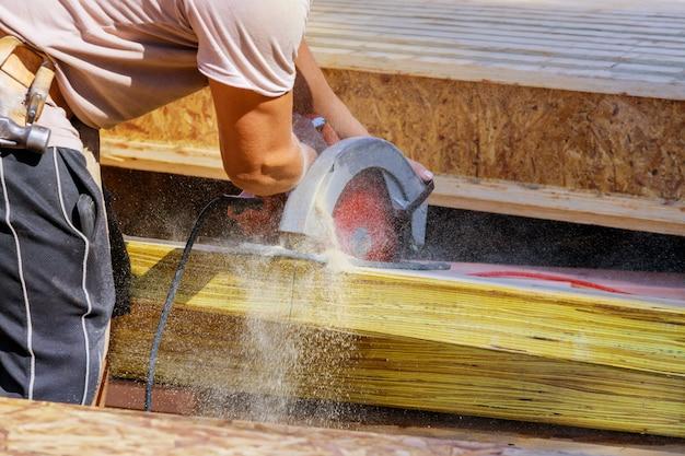 Tagliare il legno usando una sega a catena elettrica con strumenti professionali