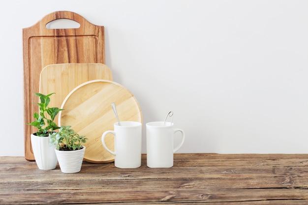 Taglio di assi di legno, tazze bianche e piante verdi sulla mensola in legno