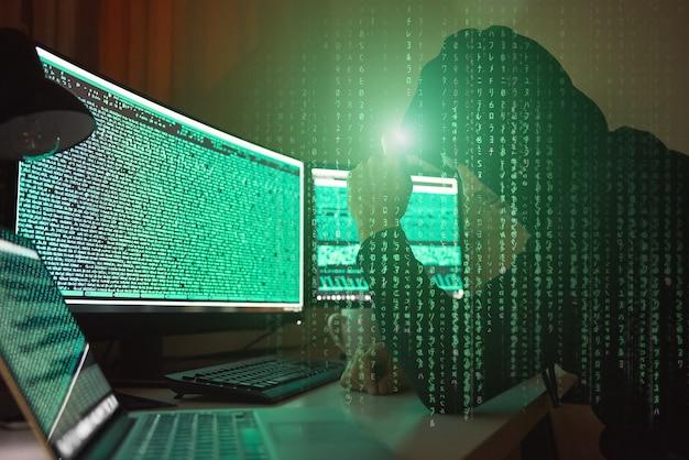 Vista laterale del crimine informatico del giovane hacker in felpa con cappuccio nera che utilizza più computer e il suo and