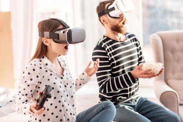 Cyberspazio. bella coppia emotiva stupita in posa sullo sfondo sfocato mentre indossa auricolari vr e uomo che tiene popcorn