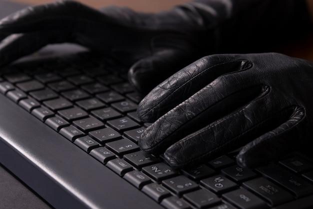 Cybercriminal mani in guanti sulla tastiera del computer portatile.
