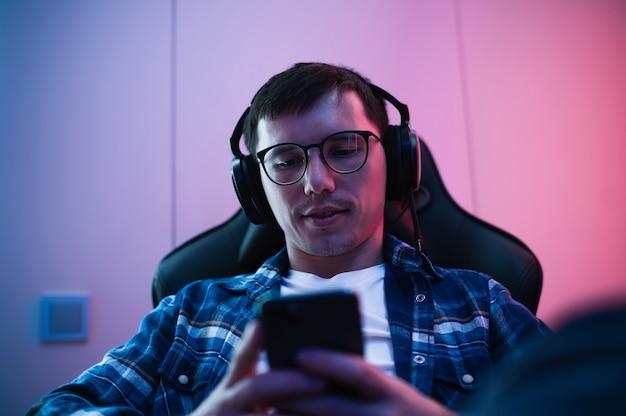 Il giocatore di cybersport ha streaming live e gioca a giochi mobili sullo smartphone a casa.