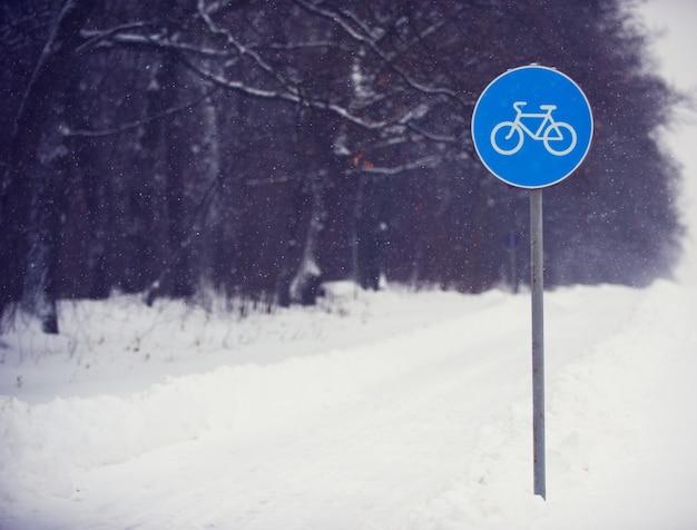 Segno della pista ciclabile coperto di neve contro una foresta scura