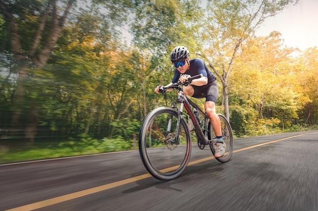 Ciclismo mountain bike ciclismo mtb sulla strada ombreggiata dalla foresta. l'atleta di mountain bike guarda la natura selvaggia in montagna. sport estremi e mtb, mountain bike downhill of motion concept.