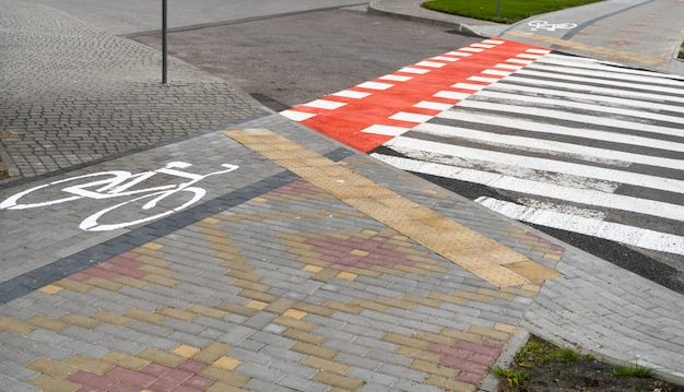 Pista ciclabile con un simbolo della bici su un terreno attraverso strada avtomobile. pista ciclabile in una città moderna.