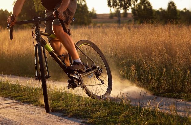 Ciclista in bicicletta solleva la polvere dalla ruota posteriore dopo una sbandata in un campo al tramonto.