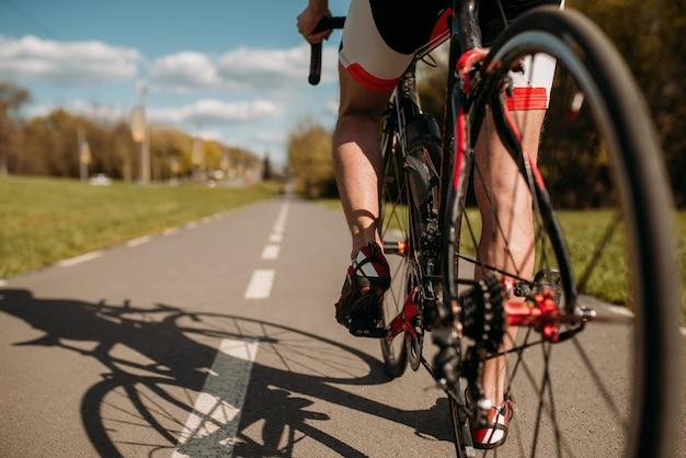 Ciclista sulla pista ciclabile, vista dalla ruota posteriore