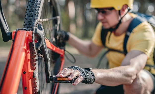 Ciclista che controlla il difetto della ruota di catena sulla bicicletta capovolta nella foresta