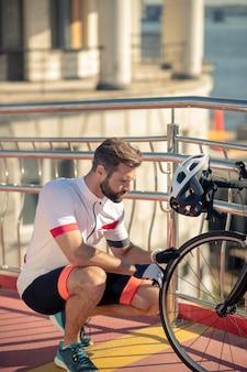 Ciclista che controlla la ruota della sua bici