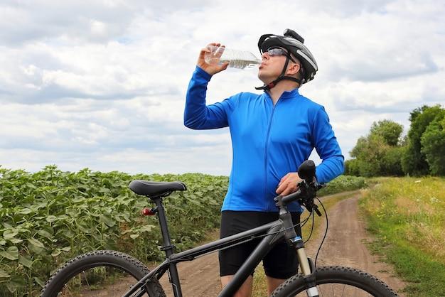Il ciclista beve l'acqua su un cielo di sfondo
