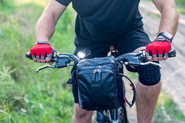 Ciclista in guanti su una mountain bike con una borsa sul manubrio.