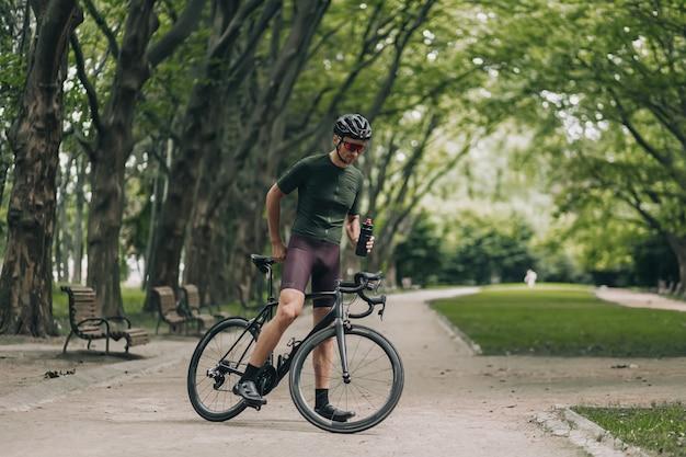 Ciclista in casco e occhiali che bevono acqua al parco