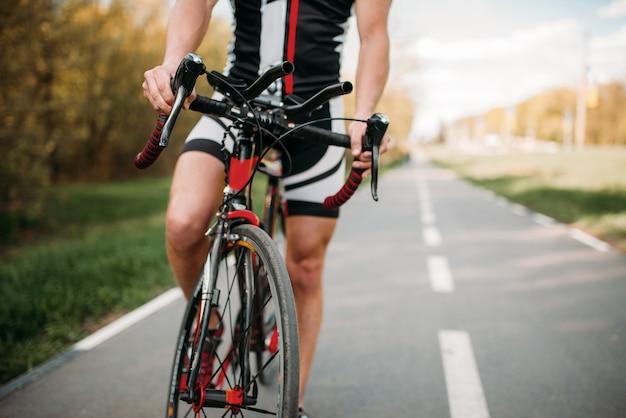 Ciclista in casco e abbigliamento sportivo, allenamento in bicicletta