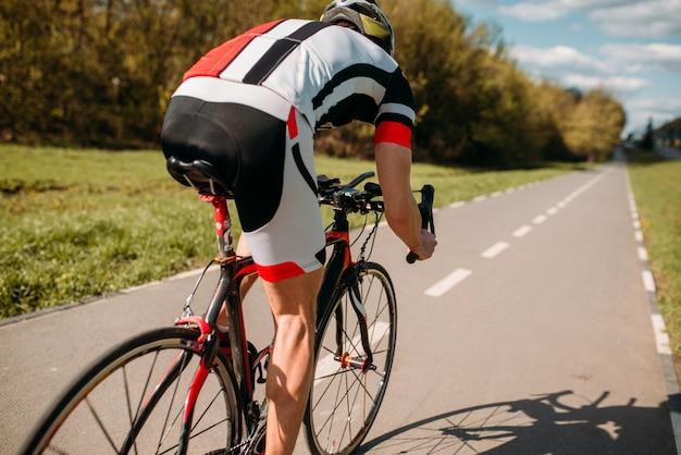 Ciclista in casco e abbigliamento sportivo cavalca in bicicletta, vista posteriore. allenamento su pista ciclabile, ciclismo