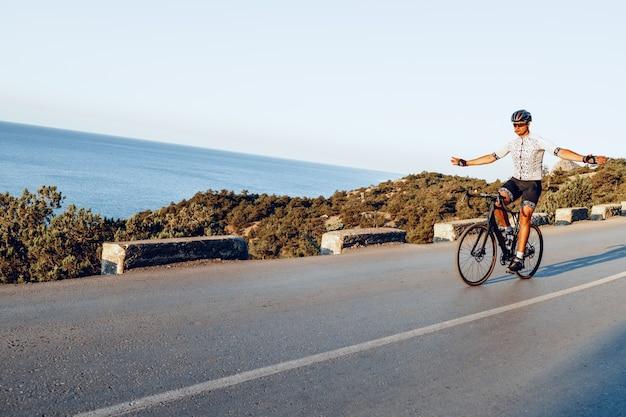 Uomo ciclista che guida sulla strada costiera all'alba