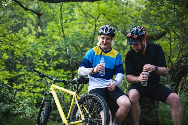 Ciclista riposo e acqua potabile nella foresta