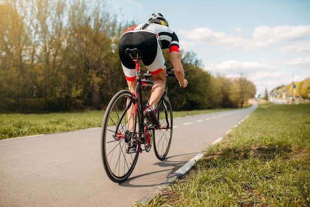 Ciclista cavalca in bicicletta, vista laterale