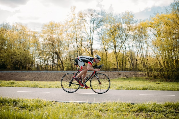 Ciclista cavalca in bicicletta, effetto velocità, vista laterale