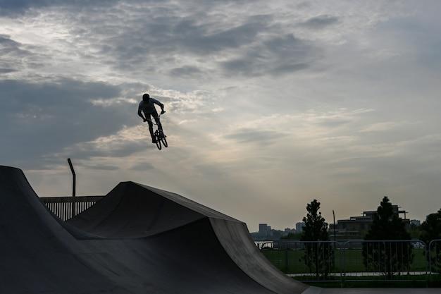Il ciclista corre in un parco estremo. lo stuntman. le rampe skate park, rollerdrome, quarter e half pipe. sport estremo, cultura urbana giovanile per attività di strada per adolescenti.