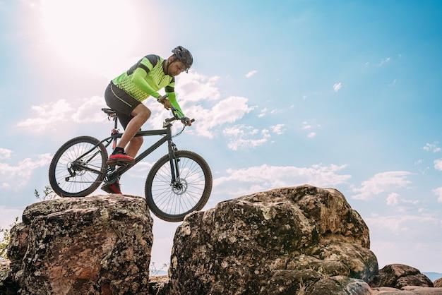 Ciclista in sella alla bici giù per la roccia in montagna. sport estremo e concetto di bicicletta da enduro.