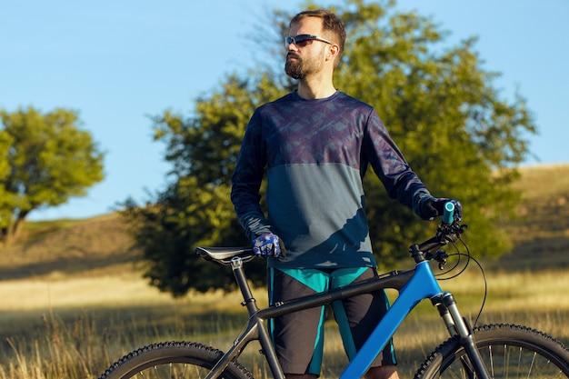 Ciclista in pantaloncini e maglia su una moderna bici hardtail in carbonio su uno sfondo di campo