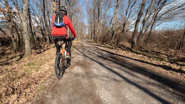 Ciclista con casco su un sentiero in campagna