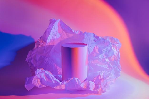 Podio cilindrico con carta stropicciata alla luce al neon. forme geometriche alla moda per mostrare i prodotti. sfondo astratto