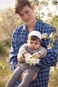 Papà in camicia a quadri tiene il figlio piccolo tra le braccia e guarda i fiori di melo sullo sfondo