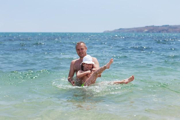 Papà e figlia che fanno il bagno, famiglia felice che riposa sul mare