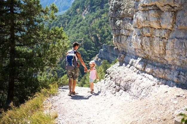 Papà e figlia fanno un'escursione su un sentiero di montagna. vacanze in famiglia attive