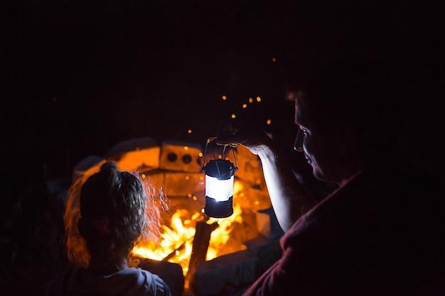 Papà e figlia si siedono di notte accanto al fuoco all'aperto in estate nella natura. campeggio in famiglia, raduni intorno al fuoco. festa del papà, barbecue. lanterna e tenda da campeggio