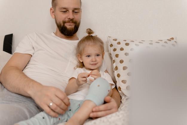 Papà e figlia che guardano video sul portatile e sorridente.