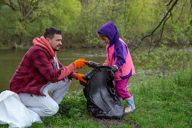 Papà e figlia, con i sacchi della spazzatura, puliscono l'ambiente dalla spazzatura.