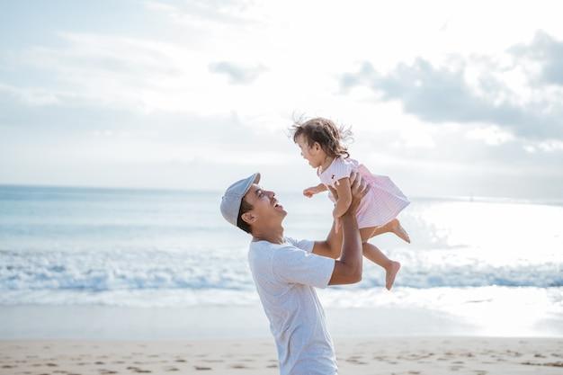 Papà si diverte a giocare con sua figlia sulla spiaggia divertendosi insieme