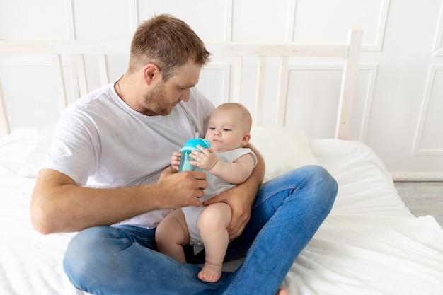 Papà nutre il figlio del bambino da una bottiglia a casa, paternità felice, concetto di pappe