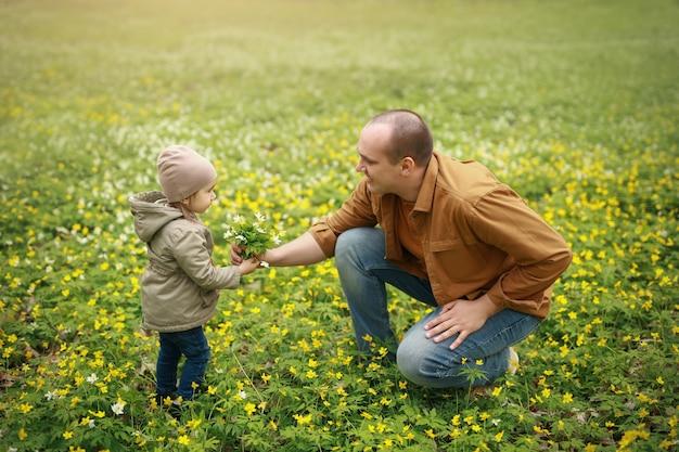 Papà regala alla figlia piccola un mazzo di fiori gialli.