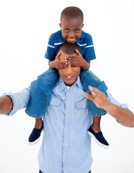 Papà che dà il figlio sulle spalle cavalcando con gli occhi chiusi